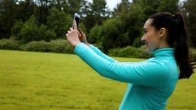 Weiblicher Rüttler, der auf einem Naturlehrpfad steht und ein lächelndes selfie mit ihrem Telefon nimmt stock video