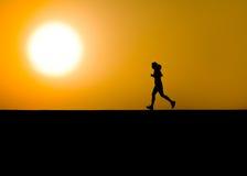 Weiblicher Rüttler im Schattenbild mit großer Sonne Stockfotografie