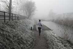 Weiblicher Rüttler am kalten nebelhaften Morgen Stockfoto