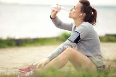 Weiblicher Rüttler-stillstehendes und trinkendes Tafelwasser Lizenzfreie Stockfotografie