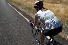 Weiblicher Radfahrer auf Land-Straße Lizenzfreies Stockbild