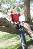 Weiblicher Radfahrer, der auf Baum während Trinkwasser sitzt Stockbild