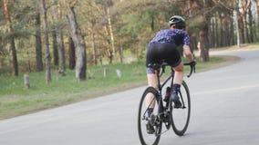 Weiblicher Radfahrer, der aus dem Sattel heraus sprintet Radfahrentrainingskonzept Ansteigende Radfahrenfahrt Langsame Bewegung