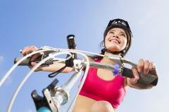 Weiblicher Radfahrer, der beginnt, mit Hintergrund des blauen Himmels zu reiten Lizenzfreie Stockfotografie