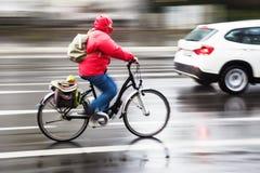 Weiblicher Radfahrer im regnerischen Stadtverkehr lizenzfreies stockbild