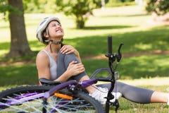 Weiblicher Radfahrer mit dem Schmerzsbein, das im Park sitzt Lizenzfreie Stockfotos