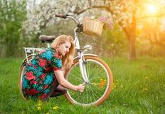 Weiblicher Radfahrer mit weißem Garten des Fahrrades der Weinlese im Frühjahr Lizenzfreies Stockbild