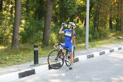 Weiblicher Radfahrer trinkt Wasser am Rennen, Bruch Lizenzfreies Stockfoto