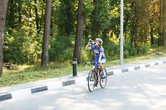 Weiblicher Radfahrer trinkt Wasser am Rennen, Bruch Stockbilder