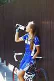 Weiblicher Radfahrer trinkt Wasser am Rennen, Bruch Stockfotografie