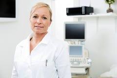 Weiblicher Radiologe-Standing In Examinations-Raum Lizenzfreies Stockfoto