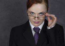 Weiblicher Rechtsanwalt, der ein großes Buch mit ernstem Ausdruck, Frau in einem Mann ` s Anzug, Bindung und Gläser hält stockfotos