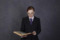 Weiblicher Rechtsanwalt liest ein großes Buch mit ernstem Ausdruck, Frau in einem Mann ` s Anzug, Bindung und Gläser stockfoto