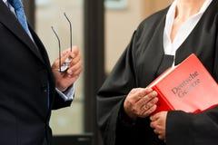 Weiblicher Rechtsanwalt mit Zivilrechtcode und Klient Stockfotografie