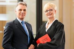 Weiblicher Rechtsanwalt mit Zivilrechtcode und Klient stockbild