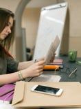 Weiblicher Rechtsanwaltlesungsvertrag mit Geschäfts-Einzelteilen herum Stockbild