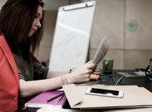 Weiblicher Rechtsanwaltlesungsvertrag mit Geschäfts-Einzelteilen herum Lizenzfreie Stockfotografie