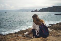 Weiblicher Reisender, der auf Meereswellen sitzt und schaut stockbilder