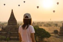 Weiblicher Reisender, der Ballone über alter Pagode betrachtet lizenzfreie stockfotografie