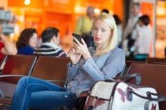 Weiblicher Reisender, der Handy bei der Aufwartung verwendet Stockfotos