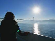 Weiblicher Reisender, der heraus Ansicht von Bosphorus-Brücke, die Türkei betrachtet Stockbilder