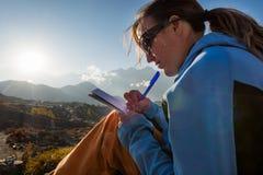 Weiblicher Reisender, der ihre Gedanken bei Sonnenuntergang schreibt Stockfoto