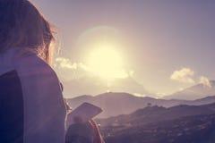 Weiblicher Reisender, der ihre Gedanken bei Sonnenuntergang schreibt Stockbild