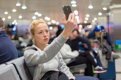 Weiblicher Reisender, der selfie auf Flughafen nimmt Lizenzfreie Stockfotos