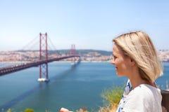 Weiblicher Reisender genießt Panoramablicke von Lissabon und von Brücke vom 25. April Lizenzfreies Stockfoto