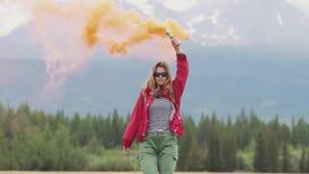 Weiblicher Reisender mit Rauchstöcken gibt ein Zeichen und erregt Aufmerksamkeit mit farbigem Rauche touristisches Mädchen, das g stock footage