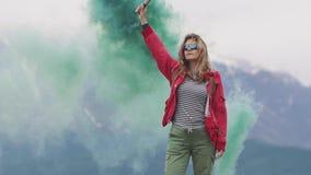 Weiblicher Reisender mit Rauchstöcken gibt ein Zeichen und erregt Aufmerksamkeit mit farbigem Rauche touristisches Mädchen, das g stock video footage