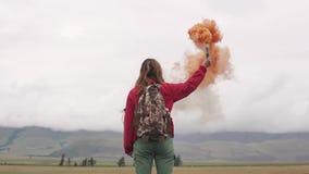 Weiblicher Reisender mit Rauchstöcken gibt ein Zeichen und erregt Aufmerksamkeit mit farbigem Rauche touristisches Mädchen, das e stock video footage