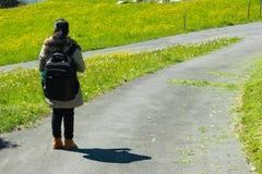 Weiblicher Reisender mit Rucksack gehend entlang Spur der grünen Straße Lizenzfreie Stockbilder