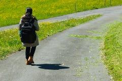 Weiblicher Reisender mit Rucksack gehend entlang Spur der grünen Straße Stockfoto