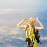 Weiblicher Reisender steht auf Hügel und schaut zum Himmel stockfotos