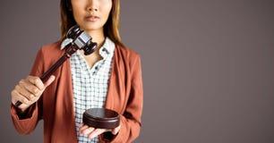 Weiblicher Richter mit Hammer gegen braunen Hintergrund lizenzfreie stockfotografie