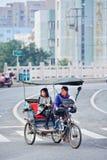 Weiblicher Rikschafahrer mit einem Passagier, der auf ein juntion, Wenzhou, China wartet stockbilder