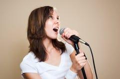 Weiblicher Sänger des Felsens auf grauem Hintergrund Stockfotos