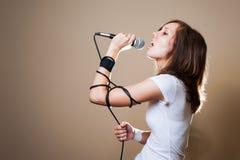 Weiblicher Sänger des Felsens auf grauem Hintergrund Lizenzfreies Stockfoto