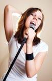 Weiblicher Sänger des Felsens auf grauem Hintergrund Stockfoto