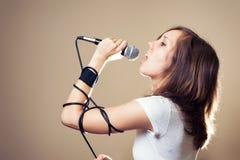 Weiblicher Sänger des Felsens auf grauem Hintergrund Lizenzfreie Stockfotos