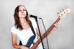Weiblicher Sänger mit Mikrofon und Bass-Gitarre auf Grau stockbild