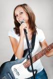 Weiblicher Sänger mit Mikrofon und Bass-Gitarre auf Grau stockfoto