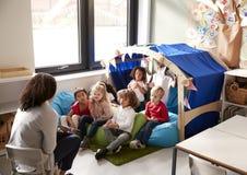 Weiblicher Säuglingsschullehrer, der auf einem Stuhl zeigt einer Gruppe Kindern ein Buch sitzen auf Bohnentaschen in einer bequem stockbilder