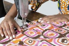 Weiblicher Schneider, der kopierten Stoff auf Nähmaschine näht Lizenzfreie Stockfotos