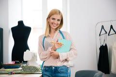 Weiblicher Schneider mit Notizbuch und Bleistift in der Werkstatt Lizenzfreies Stockfoto