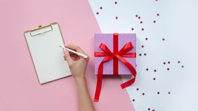 Weiblicher schreibender Wunschzettel nahe Weihnachtsgeschenk Kopieren Sie Platz lizenzfreie stockfotos
