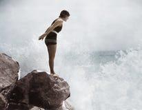 Weiblicher Schwimmer auf Felsen über zusammenstoßender Brandung (alle dargestellten Personen sind nicht längeres lebendes und kei Lizenzfreies Stockfoto