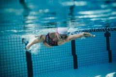 Weiblicher Schwimmer in der Aktion innerhalb des Swimmingpools Stockfotos