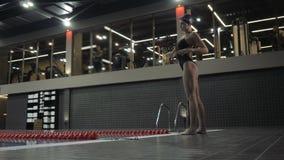 Weiblicher Schwimmer in der Badebekleidung, die das Ausdehnen der Übung für Tauchen im Swimmingpool macht stock footage